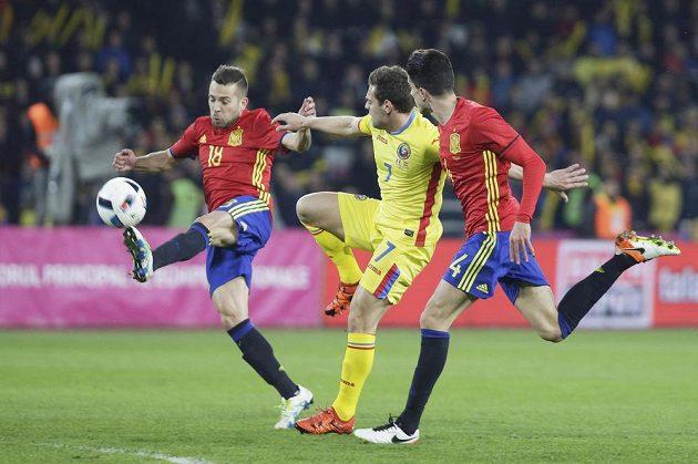 Španělští obránci Jordi Alba a Marc Bartra brání Adriana Popu z Rumunska.
