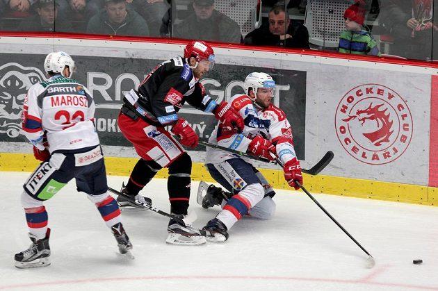 Druhý zápas čtvrtfinále play off mezi Třincem a Pardubicemi nabídl opět bojovný hokej. Třinecký David Musil se snaží prosadit proti pardubické přesile (vlevo Rostislav Marosz, vpravo Marek Trončinský).