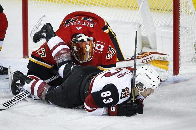 Hokejista Arizony Coyotes Conor Garland přistál na ledě a narazil do českého gólmana Davida Ritticha v brance Calgary Flames.