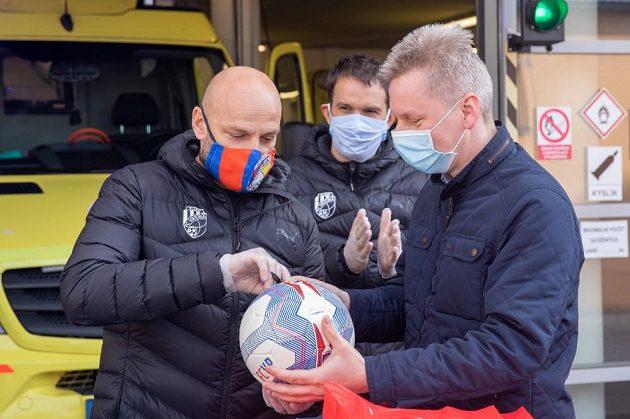 Trenér fotbalové Plzně Adrian Guľa (vpravo) podepisuje míč během poděkování Viktorie plzeňským záchranářům.