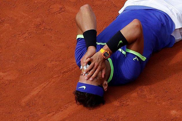 Dojatý Rafael Nadal ukrývá svou tvář v dlaních.