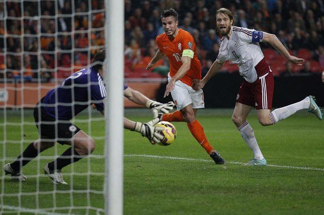 Lotyšský brankář Aleksandrs Kolinko chytá střelu Nizozemce Robina van Persieho (uprostřed), jehož se snaží bránit Kaspars Gorkss.