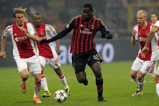 Útočník AC Milán Mario Balotelli (uprostřed) si kryje míč před Christianem Poulsenem (vlevo) z Ajaxu.