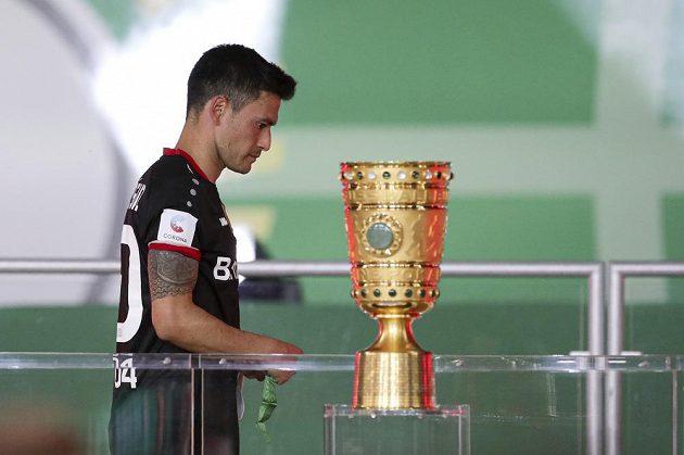 Fotbalista Leverkusenu Charles Aranguiz jde smutně kolem trofeje pro vítěze Německého poháru. Ve finále vyhrál Bayern Mnichov.