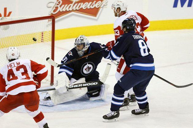 Brankář Winnipegu Ondřej Pavelec inkasuje gól z hole útočníka Detroitu Johana Franzéna (vzadu s č. 33).
