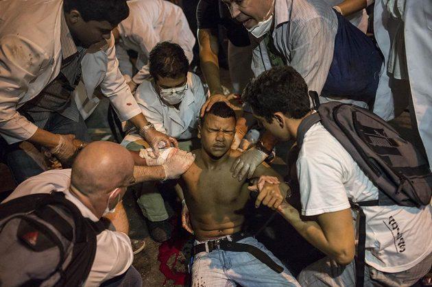 Zdravotníci ošetřují jednoho ze zasažených demonstrantů v Rio de Janeiru.
