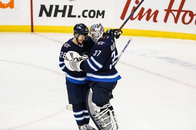 Brankář Winnipegu Connor Hellebuyck gratuluje svému spoluhráči Jack Roslovičovi k jeho hattricku v utkání NHL proti Anaheimu.