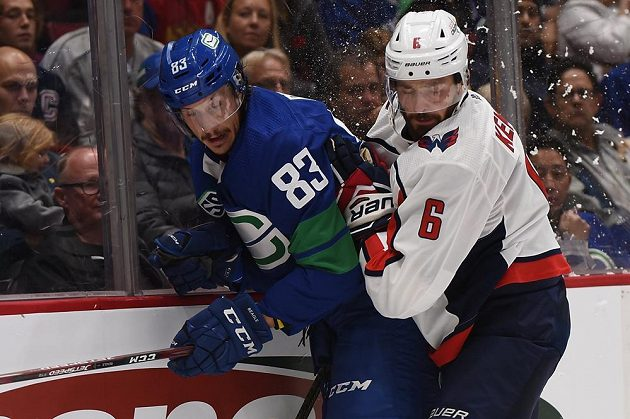 Český obránce Washingtonu Michal Kempný (v bílém) bojuje u mantinelu o puk s útočníkem Vacnouveru Jayem Beaglem během utkání NHL.