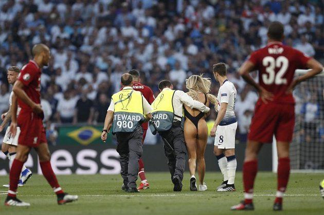 Polonahou krásku, která narušila finále fotbalové Ligy mistrů, vyprovázejí z trávníku strážci pořádku. Fotbalisté Liverpoolu vše pobaveně sledují.