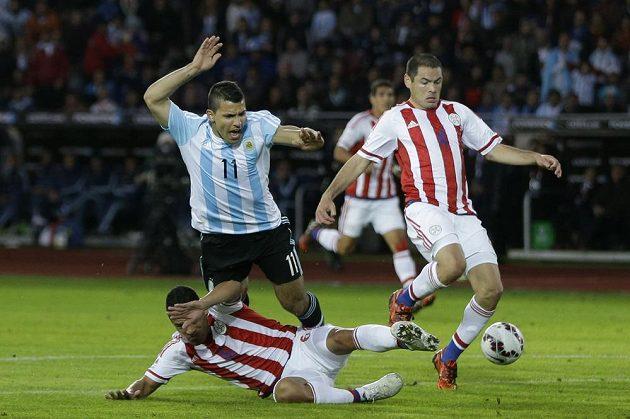 Útočník Sergio Agüero padá v souboji s paraguayskou obranou v zápase na mistrovství Jižní Ameriky.