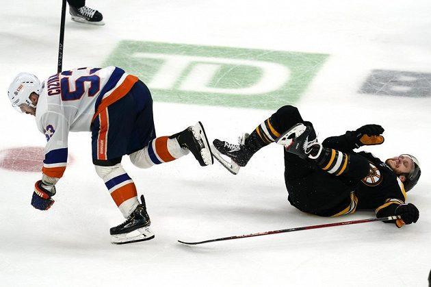 Hvězdný útočník Bostonu Bruins David Pastrňák skončil na lopatkách po souboji s Casey Cizikasem (53) z týmu New York Islanders během utkání NHL.