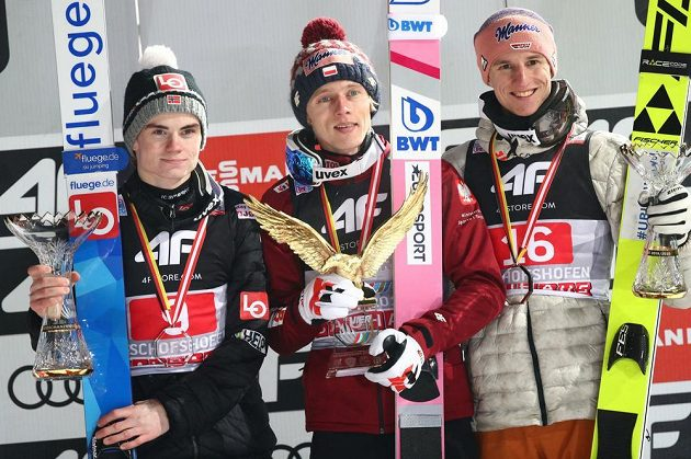 Polský skokan na lyžích Dawid Kubacki slaví premiérový triumf na Turné čtyř můstků. Na snímku mu dělají společnost druhý Nor Marius Lindvik a třetí Němec Karl Geiger.