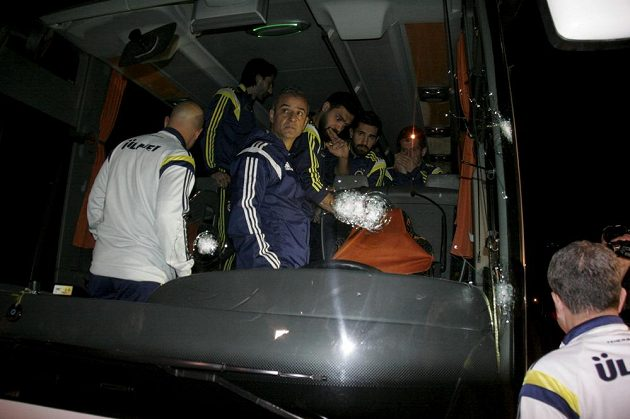 Hráči Fenerbahce Emre Belezöglu, Alper Potuk, Bekir Irtegün a trenér Ismail Kartal si nevěřícně prohlížejí prostřílené sklo autobusu a zasažené místo řidiče.