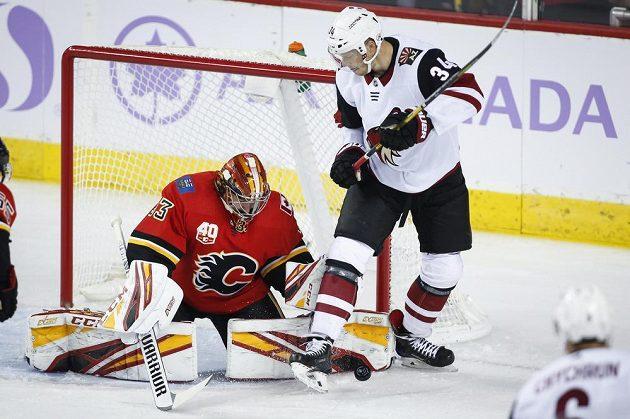 Hokejista Arizony Coyotes Carl Soderberg zkouší rozhodit českého gólmana Davida Ritticha z Calgary Flames.