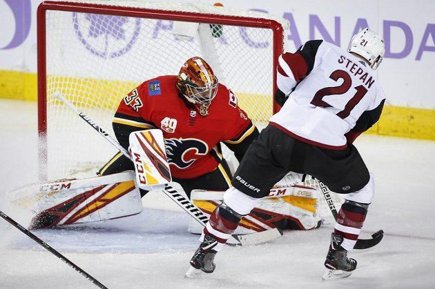 Hokejista Arizony Coyotes Derek Stepan zkouší vyzrát na Davida Ritticha v brance Calgary Flames.
