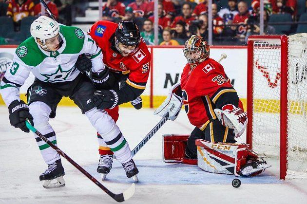 Brankář hokejistů Calgary Flames David Rittich sleduje, jak touš míjí jeho branku v utkání NHL.