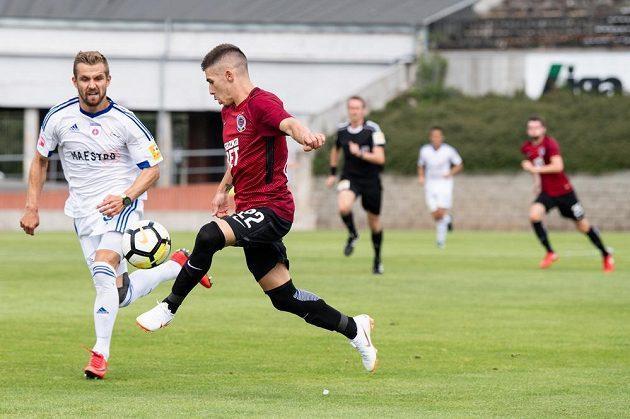 Fotbalista Sparty Srdjan Plavšič odehrává míč před Dominikem Kuncou z Ružomberku během přípravného utkání.