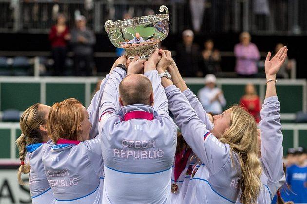 České tenistky v čele s kapitánem Petrem Pálou (uprostřed) zdvihají pohár pro vítězky Fed Cupu.