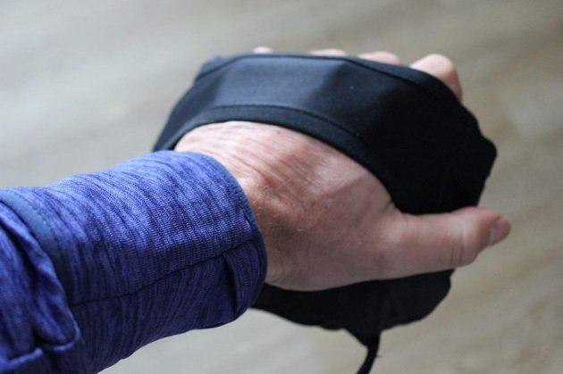 Vesta Nike Aeroloft Flash: Na ruce sbalenou vestu drží široký pružný popruh.