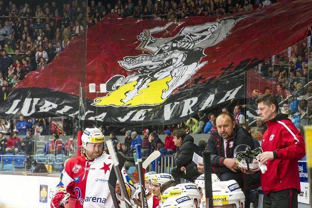 Trenér Slavie Ladislav Lubina (druhý zprava na střídačce), za ním fanoušci s transparentem.