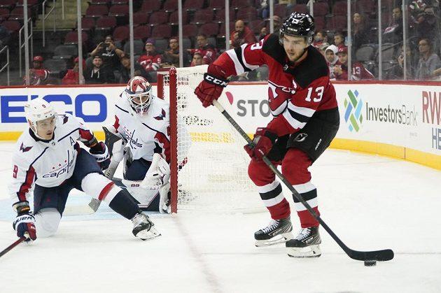 Brankář Washingtonu Capitals Vítek Vaněček a obránce Capitals Dmitrij Orlov sledují akci Nico Hischiera z New Jersey Devils před startem NHL.
