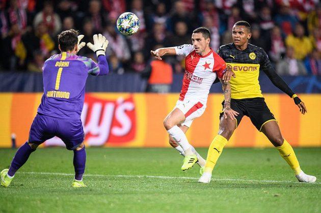 Brankář Dortmundu Roman Bürki se chstá chytit míč, dobíhá Nicolae Stanciu ze Slavie a Manuel Akanji z Dortmundu během utkání základní skupiny Ligy mistrů v Praze.