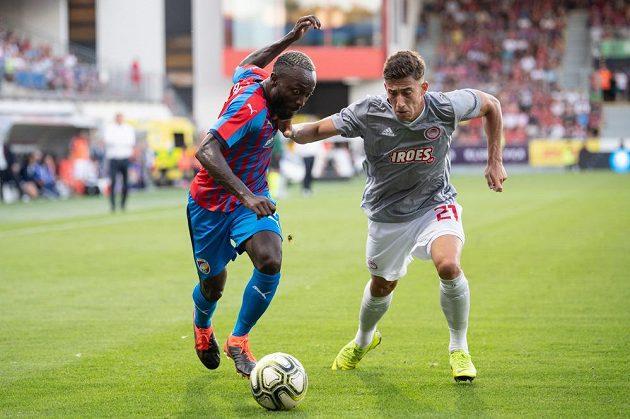 Joel Kayamba z Viktorie Plzeň a Konstantinos Tsimikas z Olympiakosu v akci během utkání 2. předkola Ligy mistrů.