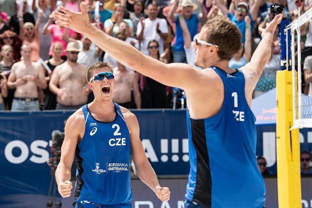 Čeští beachvolejbalisté David Schweiner (vlevo) a Ondřej Perušič oslavují vítězství a postup do čtvrtfinále turnaje J&T Banka Ostrava Beach open 2019.