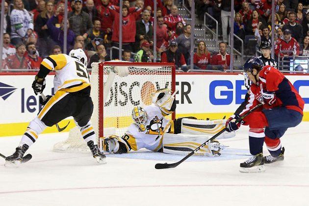 Útočník Washingtonu T. J. Oshie překonává brankáře Pittsburghu Matta Murrayho. Vlevo přihlíží obránce Penguins Kris Letang.