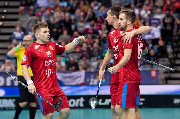 Čeští florbalisté (zleva): Martin Pražan, Jiří Bauer a Patrik Dóža oslavují gól proti Dánsku ve čtvrtfinále MS.