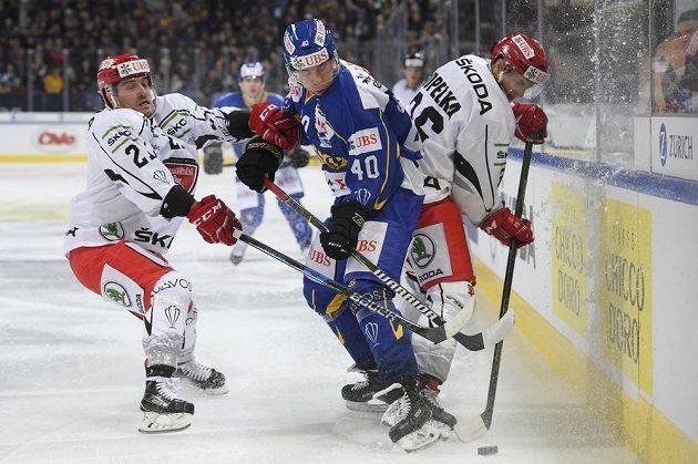 Tomi Sallinen (uprostřed) z Davosu bojuje o puk s královéhradeckými hráči Petrem Koukalem (vlevo) a Lukášem Vopelkou.