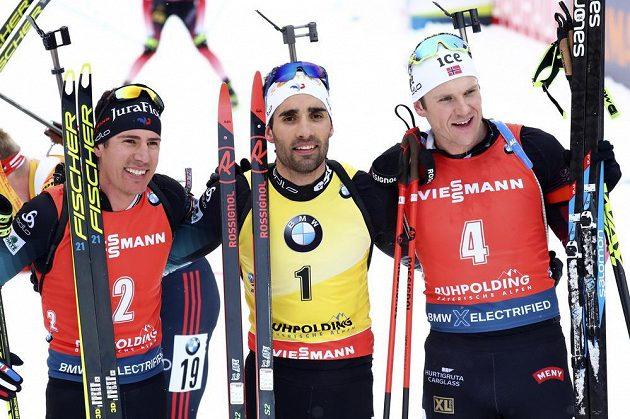 Francouz Martin Fourcade vyhrál stíhačku biatlonistů v Ruhpoldingu. Vlevo na fotce je druhý muž v cíli Quentin Fillon Maillet z Francie a vpravo třetí Vetle Sjaastad Christiansen.