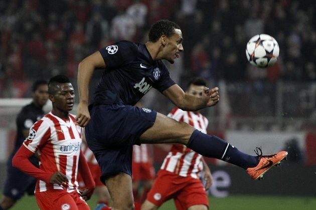 Rio Ferdinand z Manchesteru United v utkání Ligy mistrů odkopává míč, vlevo přihlíží Michael Olaitan z Olympiakosu Pireus.