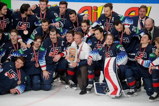 Američtí hokejisté pózují s trofejí pro bronzové medailisty rižského šampionátu.