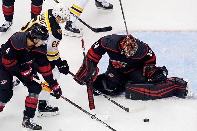 Centr Bostonu Bruins Jack Studnicka (68) před brankou Caroliny Hurricanes, kterou střežil český gólman Petr Mrázek.