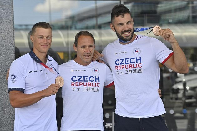 Deblkajakáři Josef Dostál (vpravo) a Radek Šlouf (vlevo) pózují fotografům s trenérem Karlem Leštinou (uprostřed) a bronzovými medailemi na Letišti Václava Havla v Praze po příletu z letních olympijských her v Tokiu.