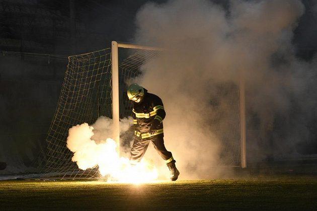 Jeden z hasičů sbírá z hřiště světlice, které tam v úvodu utkání naházeli fanoušci Sparty.