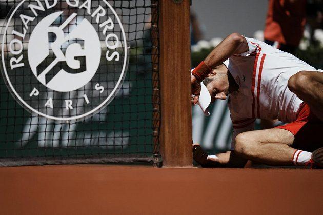 Srbský tenista Novak Djokovič se zvedá z antuky během finále French Open, když upadl při dobíhání kraťasu.