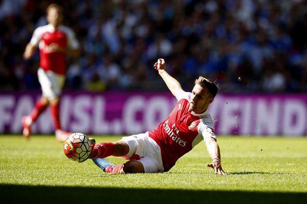 Záložník Arsenalu Aaron Ramsey skluzem získává míč pro svůj tým.