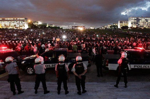 Policisté dohlížejí na demonstranty v hlavním městě Brazílie Brasilii.