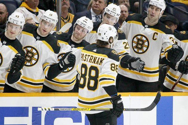 Český útočník David Pastrňák slaví se spoluhráči z týmu Boston Bruins gól vstřelený v utkání NHL.