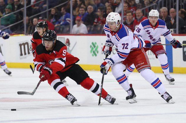 Křídelní útočník New Jersey Devils Taylor Hall (9) se snaží s pukem uniknout českému mladíkovi Filipu Chytilovi v barvách New Yorku Rangers během utkání NHL.