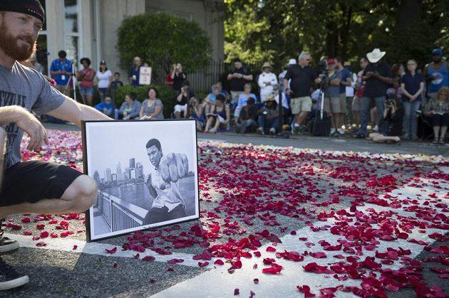 Jeden z fanoušků s potrétem Muhammada Aliho u hřbitova.