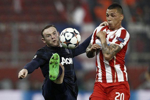 Útočník Manchesteru United Wayne Rooney (vlevo) bojuje o míč s Josém Holebasem z Olympiakosu Pireus.
