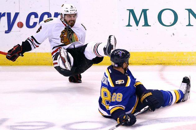 Český zadák Chicaga Michal Kempný (vlevo) padá na led po srážce s Kylem Brodziakem ze St. Louis.