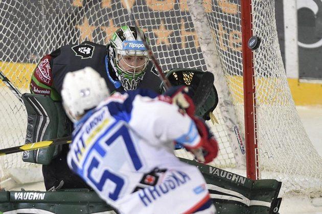 Brněnský hokejista Jan Hruška (vpředu) pálí na brankáře Mladé Boleslavi Pavla Kantora během extraligového utkání.