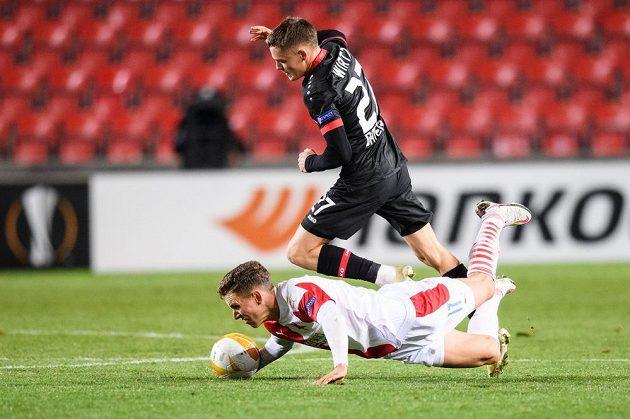 Florian Wirtz z Leverkusenu a Lukáš Provod (na zemi) ze Slavie během utkání základní skupiny Evropské ligy v Praze.