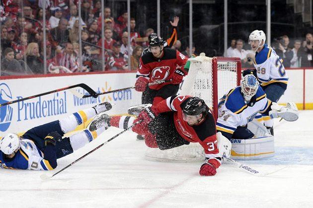 Souboj českého centra Pavla Zachy v dresu New Jersey (37) a švédského útočníka Oskar Sundqvista ze St. Louis (v bílém) během druhé třetiny zápasu NHL.
