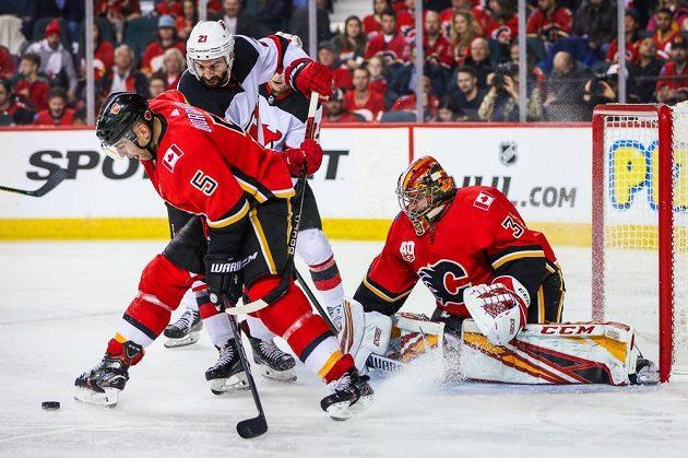 Závar před brankou českého gólmana Calgary Davida Ritticha během utkání NHL.