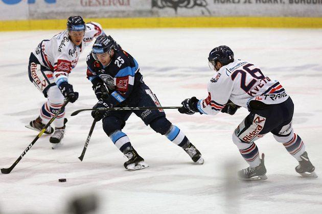 Liberecký hokejista Radan Lenc z Liberce se snaží prosadit mezi dvojicí hráčů Vítkovic během utkání 38. kola extraligy